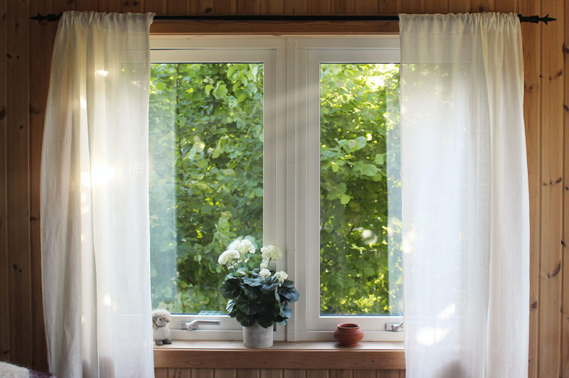window facing greenery with white curtains